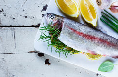 Raw rainbow trout. Old white wooden table with fresh raw rainbow trout on marble board with lemon, herbs and spices, top view, copy space. Seafood cooking Royalty Free Stock Images