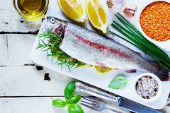 Raw rainbow trout. Old white wooden table with raw rainbow trout, vegetables, grains, herbs and spices on marble board, top view, copy space. Seafood cooking stock photos
