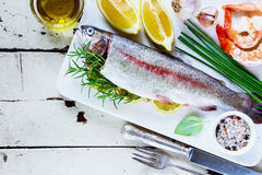 Raw rainbow trout. Seafood with ingredients on white old wooden table. Fresh raw rainbow trout and shrimps over marble board with lemon, herbs and spices, top Stock Images