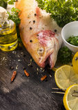 Raw rainbow trout with spices and lemon , preparation. Raw rainbow trout with spices and lemon on dark wooden table, preparation Stock Photos