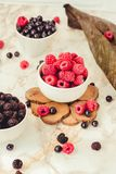 Raw raspberries and blueberries in white cups. Summer fruit, berries. Detox diets and healthy food concept. Tone. stock image