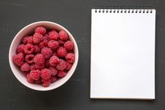 Raw raspberries in a pink bowl, blank notepad over black surface, top view. From above, overhead. Copy space stock image