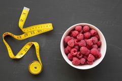 Raw raspberries in a pink bowl with measuring tape on black surface, top view. Healthy eating and dieting. From above, overhead stock image