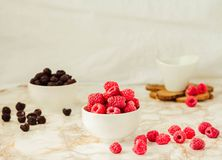 Raw raspberries and wild black, blackberries in white cups. Light marble background. Place for text. Detox diets and healthy food. Concept royalty free stock image