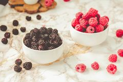 Raw raspberries and wild black, blackberries in white cups. Light marble background. Summer fruit, berries. Detox diets and. Healthy food concept.Tone stock photography