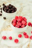 Raw raspberries and wild black, blackberries in white cups. Light marble background. Summer fruit, berries. Detox diets and. Healthy food concept.Selective royalty free stock images