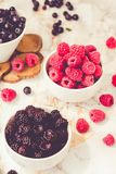 Raw raspberries and wild black, blackberries in white cups. Light marble background. Summer fruit, berries. Detox diets and. Healthy food concept.Tone royalty free stock photos