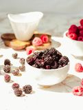Raw raspberries and wild black, blackberries in white cups. Light marble background. Summer fruit, berries. Detox diets and. Healthy food concept.Sunlight stock photos