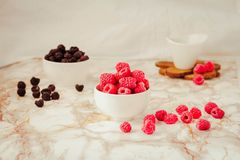 Raw raspberries and wild black, blackberries in white cups. Light marble background. Place for text. Detox diets and healthy food. Concept.Selective focus royalty free stock photo