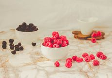 Raw raspberries and wild black, blackberries in white cups. Light marble background. Place for text. Detox diets and healthy food. Concept.Toning stock image