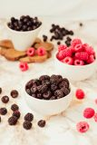 Raw raspberries and wild black, blackberries in white cups. Light marble background. Summer fruit, berries. Detox diets and. Healthy food concept.Selective royalty free stock photography