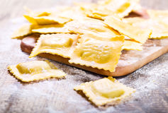 Raw ravioli with flour. On wooden table Stock Photo