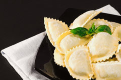 Raw ravioli over black plate Royalty Free Stock Image