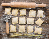 Raw ravioli on wooden background. Raw ravioli and tools for their preparation on wooden background Stock Photography