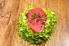 Raw beef with sald and pepper grains Royalty Free Stock Images