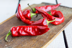 Raw red chili pepper on a cutting board, spices. On a wooden board Royalty Free Stock Photo