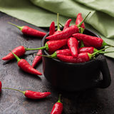 Raw red chili peppers on a black rusty table. Food and drink, still life, moody concept. Raw red mexican chili peppers on a black rusty table. Selective focus Stock Image