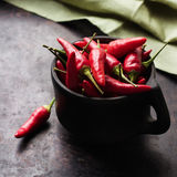 Raw red chili peppers on a black rusty table. Food and drink, still life, moody concept. Raw red mexican chili peppers on a black rusty table. Selective focus Royalty Free Stock Images