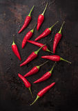 Raw red chili peppers on a black rusty table. Food and drink, still life, moody concept. Raw red chili peppers on a black rusty table. Selective focus top view Royalty Free Stock Photos