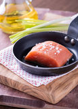 Raw red fish fillet with sea salt on frying pan. Selective focus Royalty Free Stock Photo