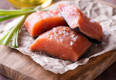 Raw red fish fillet. With sea salt over wooden board, selective focus Royalty Free Stock Images