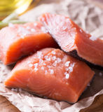 Raw red fish fillet. With sea salt over wooden board, selective focus Stock Photos