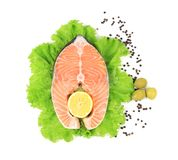 Raw red fish and lemon  on salad. Backgrounde on white Royalty Free Stock Photography