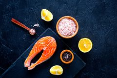 Raw red fish steak. Peiece of fresh salmon on cutting board near sea salt, pepper, lemon slices on black background top. View Royalty Free Stock Photography