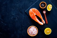Raw red fish steak. Peiece of fresh salmon on cutting board near sea salt, pepper, lemon slices on black background top. View Stock Photos