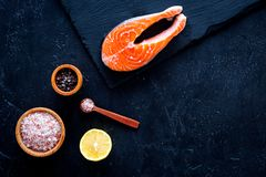 Raw red fish steak. Peiece of fresh salmon on cutting board near sea salt, pepper, lemon slices on black background top. View Stock Images
