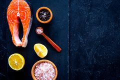 Raw red fish steak. Peiece of fresh salmon on cutting board near sea salt, pepper, lemon slices on black background top. View Royalty Free Stock Images