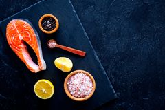 Raw red fish steak. Peiece of fresh salmon on cutting board near sea salt, pepper, lemon slices on black background top. View Royalty Free Stock Photos