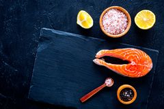 Raw red fish steak. Peiece of fresh salmon on cutting board near sea salt, pepper, lemon slices on black background top. View Royalty Free Stock Image