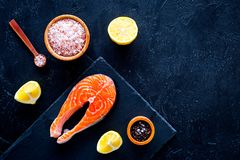 Raw red fish steak. Peiece of fresh salmon on cutting board near sea salt, pepper, lemon slices on black background top. View Stock Photo