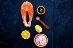 Raw red fish steak. Peiece of fresh salmon on cutting board near sea salt, pepper, lemon slices on black background top. View Stock Image
