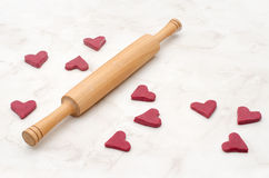 Raw red heart-shaped cookies on a white table with a rolling pin, baking for Valentine's Day Stock Images