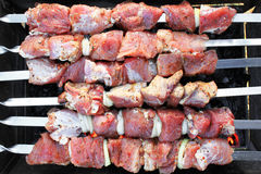Raw red meat on barbecue close-up as gastronomic background for showcase of meat shop, restaurant or cafe. Raw red meat on barbecue close up as gastronomic Royalty Free Stock Image
