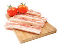 Raw red meat fat bacon and tomato on a wooden board isolation on. White Stock Image