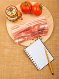 Raw red meat fat bacon, tomatoes and notebook on a wooden board. On the canvas Stock Images