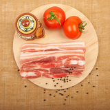 Raw red meat fat bacon, tomatoes and spices on a wooden board on. The canvas Stock Photo