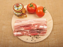 Raw red meat fat bacon, tomatoes and spices on a wooden board on. The canvas Royalty Free Stock Photo