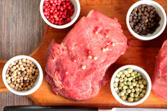 Raw red meat ready for pepper steak cooking on the kitchen board. With colored peppers - black, rose, green (pepe verde) and white Royalty Free Stock Photography
