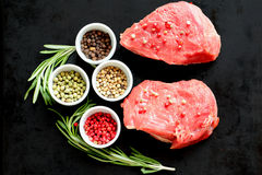 Raw red meat ready for pepper steak cooking on the kitchen board with colored peppers - black, rose, green and white. Raw red meat ready for pepper steak cooking Stock Photo
