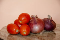 Raw red onions and tomatoes. On wooden table Royalty Free Stock Photography
