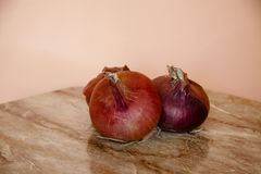 Raw red onions. On wooden table Royalty Free Stock Images