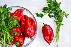 Raw red organic peppers with bunch of aromatic green spice parsley in a glass bowl ready to cook with Royalty Free Stock Photos