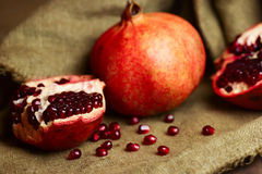 Raw red pomegranate with seeds on sacking Royalty Free Stock Image