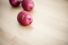 Raw red potatoes on wood table Royalty Free Stock Photos