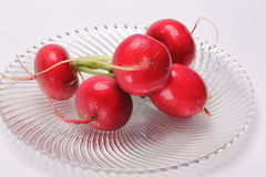 Raw red radishes on glass plate. Raw radishes on a fluted glass plate Royalty Free Stock Photos