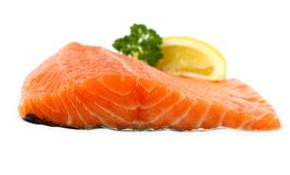 Raw, red salmon fillet with lemon wedge, frontal Stock Image
